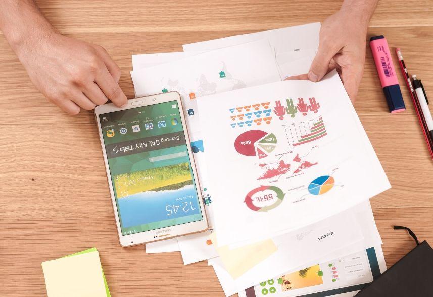 Relatório Instagram: imagem de algumas folhas de papel com gráficos impressos em cima de uma mesa de madeira, um celular e uma mão mexendo no celular