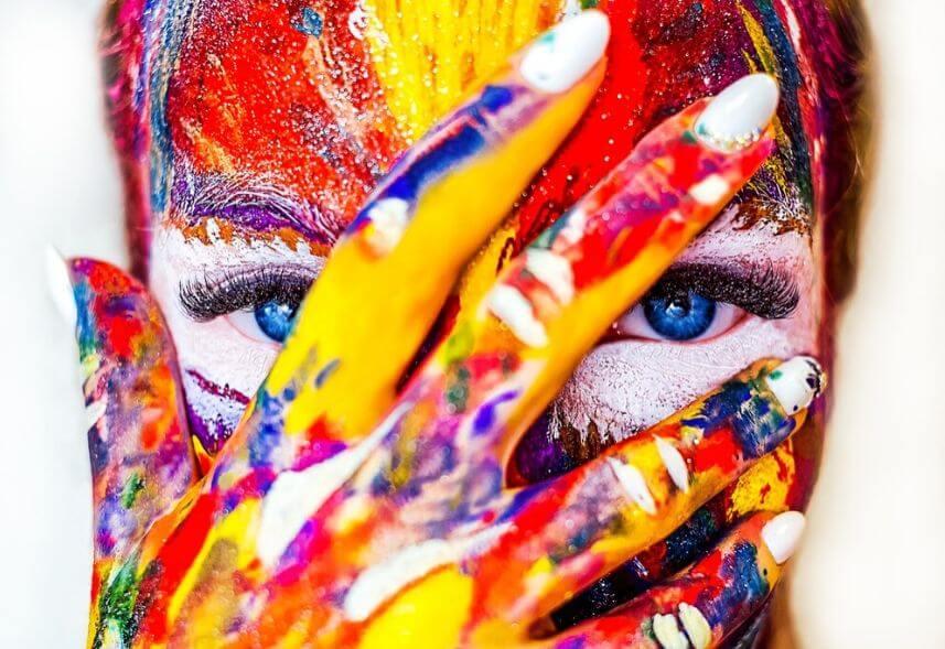 Cores no Marketing: imagem do rosto de uma mulher todo pintado de tinta com as cores azul, amarela, vermelho