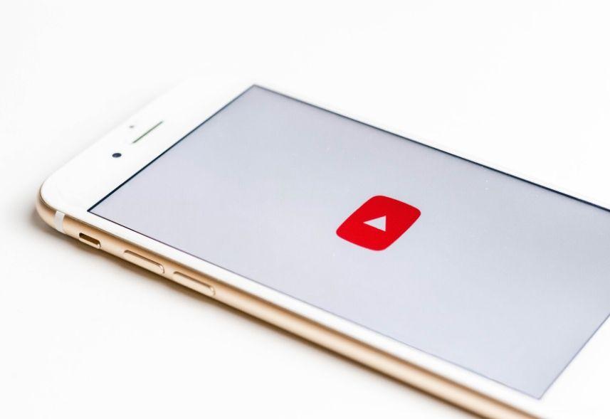 """Tags para YouTube: imagem de um celular com a tela aberta e um ícone de """"play"""" para começar um vídeo"""