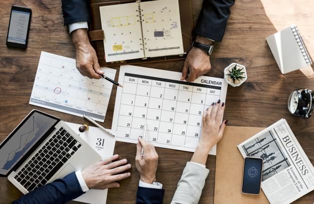 E-mail marketing e redes sociais: imagem de uma mesa de reunião com três pessoas discutindo com as mãos sob um calendário de papel