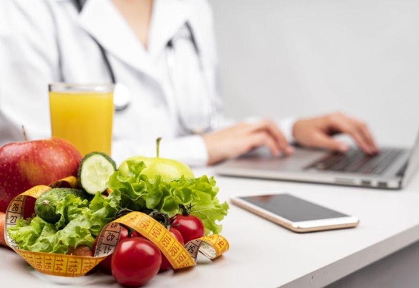 marketing para nutricionista: imagem de um mulher digitando no notebook ao fundo e uma seleção de frutas e verduras e um suco de laranja com uma fita métrica na frente