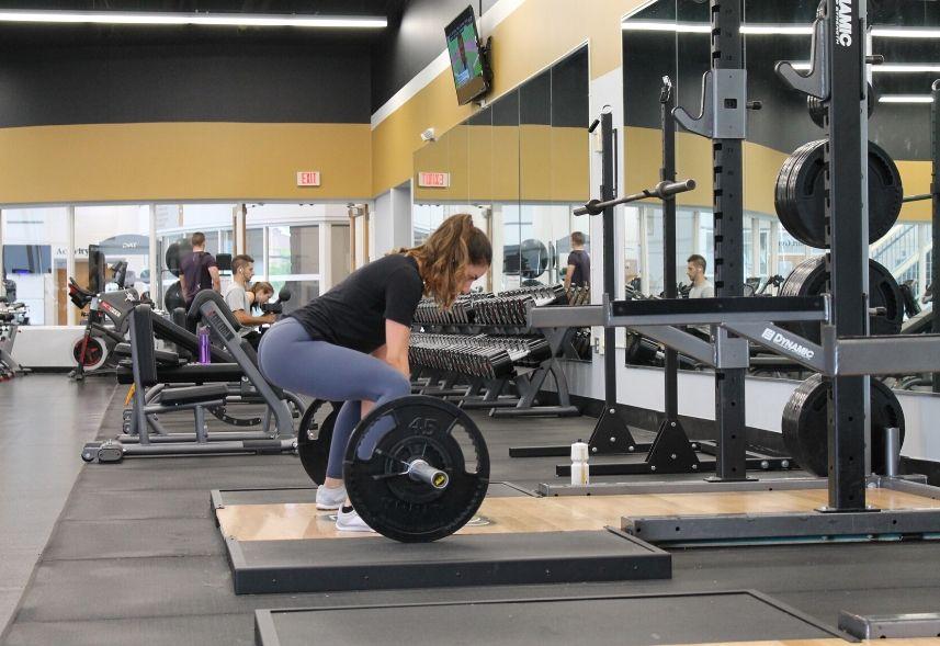 Marketing para academia: imagem de uma academia com um mulher levantando peso e outras pessoa no fundo em outros aparelhos