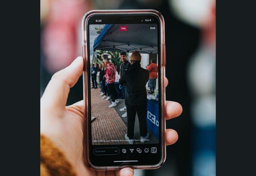 como fazer live no Instagram: imagem de uma mão segurando um celular com uma live na tela