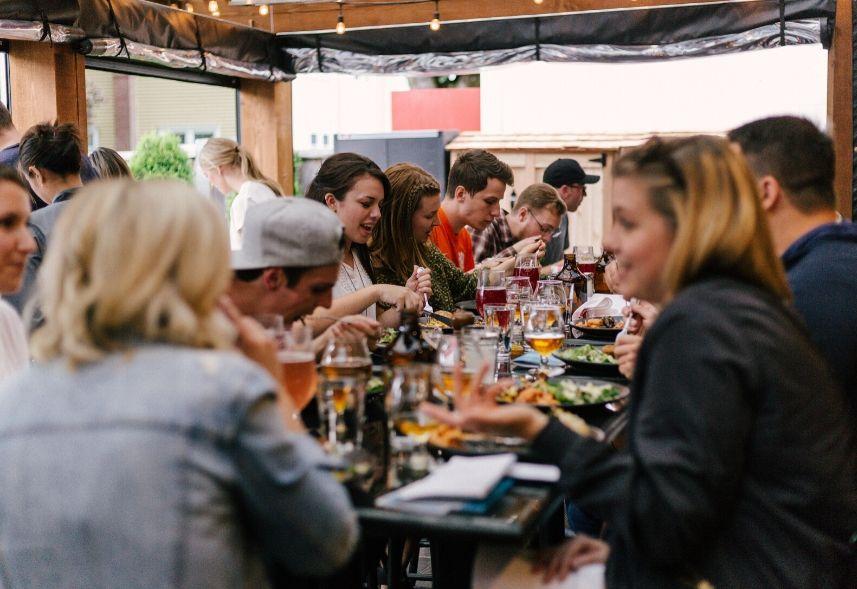 Redes sociais para restaurantes: imagem de várias pessoas sentadas em mesas fazendo refeições dentro de um restaurante
