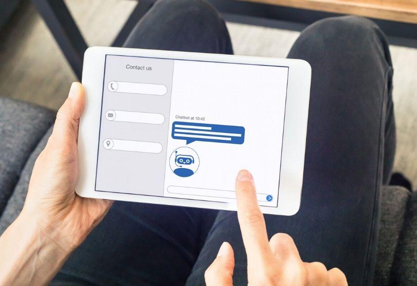 O que é chatbot: imagem de duas mãos segurando um tablet realizando um antedimento via chatbot na tela
