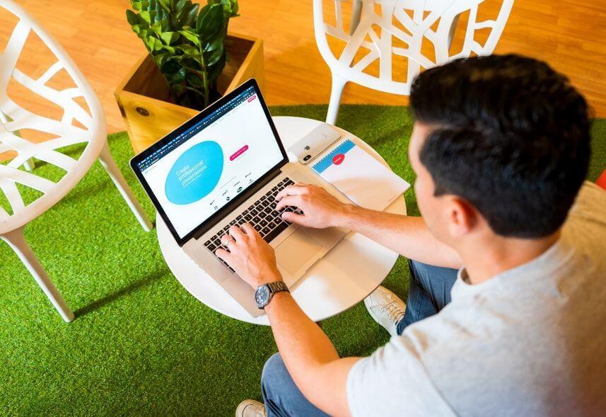 Gestor de mídias sociais: imagem de um homem sentado na cadeira digitando em um notebook sob uma mesa