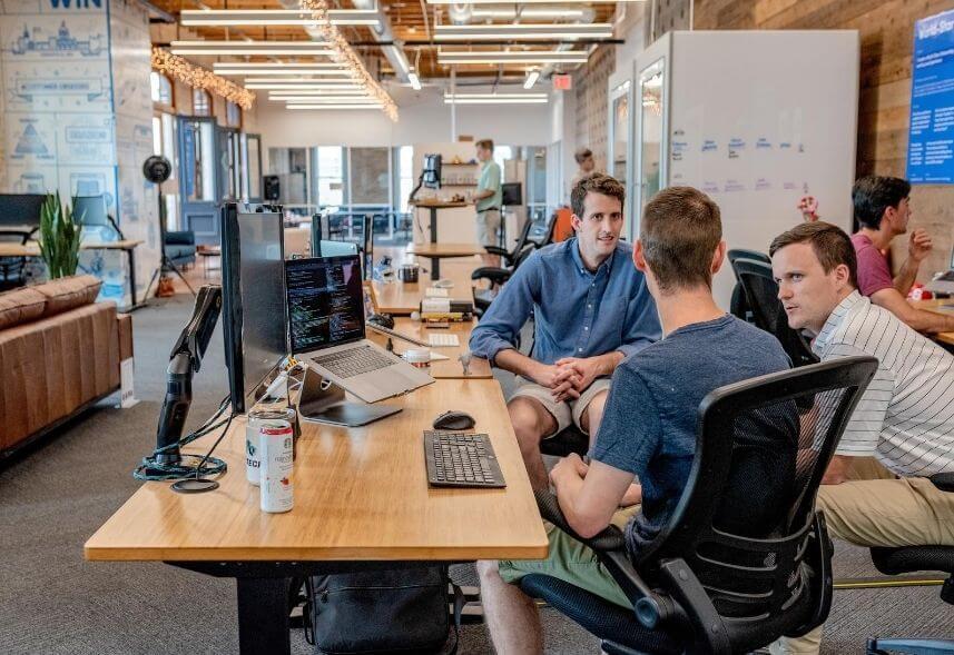 Marketing de afiliados: imagem de três homens conversando em reunião dentro de um ambiente de agência