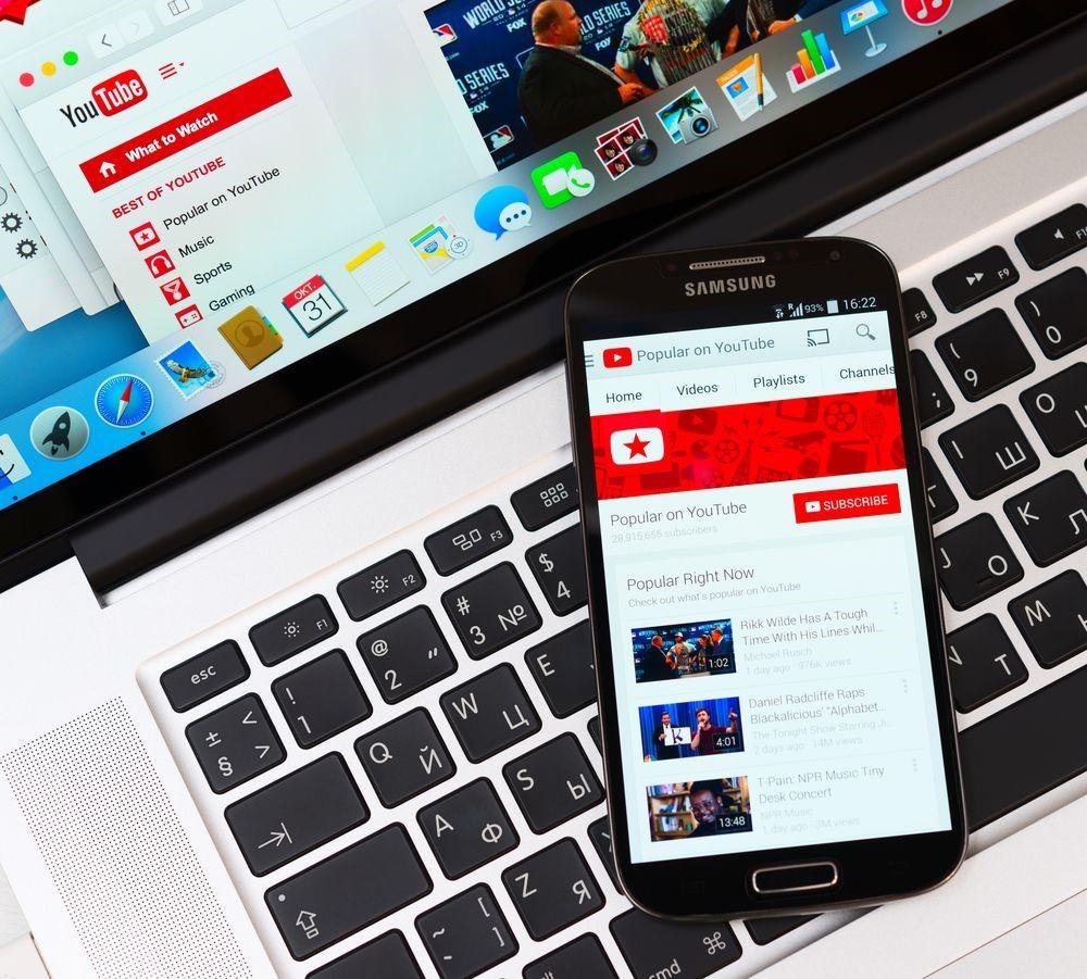 Como vender nas redes sociais: imagem de um notebook e um celular sobre o teclado do notebook com a tela do youtube aberta