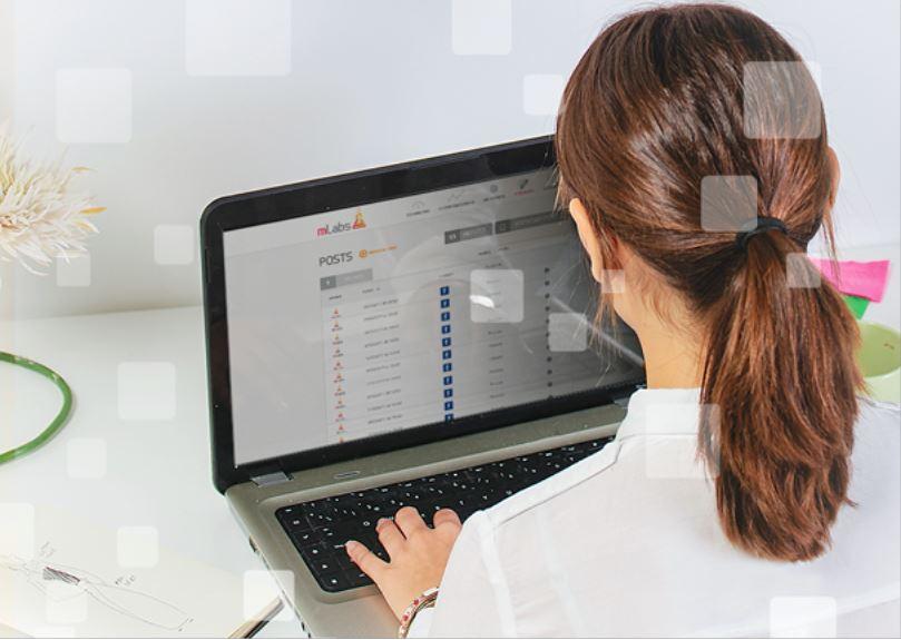 postagem automatica instagram: imagem de uma mulher sentada digitando em um notebook com a página de posts da mLabs aparecendo na tela