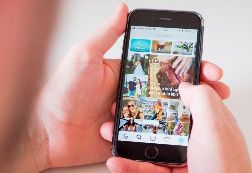 publicidade no instagram: imagem de uma mão segurando o celular com a tela do explorar do instagram aberta mostrando vários posts