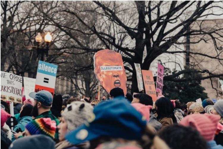 O papel das redes sociais nas discussoes politicas: uma foto de uma manifestação que reuni uma dezena de pessoas nas ruas, é possível ver galhos de uma árvore sem flores ao fundo e, diante dela, as pessoas carregam cartazes de insatisfação política.