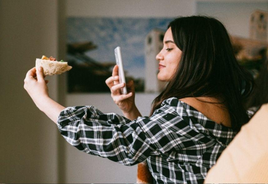 O que e UGC: na foto, uma moça branca está segurando o celular e apontando para uma pão segurada por sua outra mão. Ela está fotografando a comida.