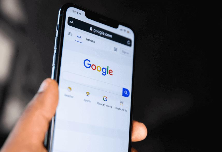 como criar conta no google ads: imagem de uma mão segurando um celular com a tela do Google a mostra