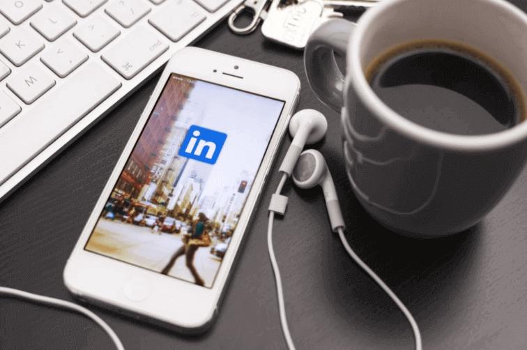o que é linkedin: imagem de um celular com fone de ouvido plugado em cima de uma mesa com a tela do linkedin aberta e uma xícara de café ao lado