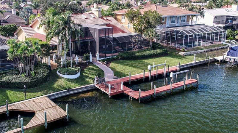 Welcome home to this beautiful WATERFRONT home with BAY & GULF access in the GATED community of Bayside! As you open the front door, you are greeted by SPECTACULAR WATER VIEWS, floating staircase & a great room with 2 STORY CEILINGS! The owners have spent over 275k renovating & adding an extension onto the home of approximately 750 sq ft. to include a BONUS/GAME room OR 6TH BEDROOM. THE MASTER BEDROOM IS DOWNSTAIRS, as well as most of the home, w/ upstairs consisting of just 2 bedrooms, a beautifully renovated bathroom, loft & a BALCONY DECK stretching across the entire back of the 2nd story. Downstairs you will find all else including an office/den opening up to the great room w/ an open bar, WINE FRIDGE, & ice maker. The formal dining room is just off kitchen w/ a butlers pantry. Kitchen was completely renovated w/ granite counters, wood cabinets, SS appliances & hard wood flooring. The spacious master has 2 walk in closets, GAS FIREPLACE & beautiful water views right from your bed! Master bath has granite, dual vanity, garden tub & walk in shower. All across the back of the home are sliding pocket doors opening the rooms to the outside pool area. Fabulous STACKED STONE OUTSIDE BAR as well as grilling station & fun pool area. Made for entertaining! GREAT DOCK AND BOAT LIFT to enjoy your FL lifestyle! Excellent location,10 mins to airport,20 mins downtown, great schools ,only 5 mins to Berkeley Prep. EASY ACCESS TO BOTH SIDES OF THE BAY! Lots of fun in the neighborhood, yacht club & LIGHTED BOAT PARADE