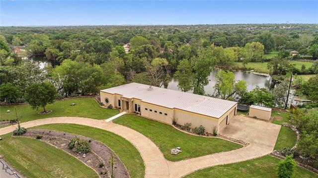 Beautiful custom home built on 2.18 acres with private lake on property! Panoramic wildlife and water views across the rear of your home and an extended patio with fireplace, cook area & bar. Inside, your spacious home has living room with fireplace, large kitchen, bonus room, office, huge walk-in pantry and lots of storage space. Master has walk-in shower, jetted-tub and two huge closets. Large garage with 4 bays has plenty or room for toys or projects. Walk to Walsh MS and enjoy great RRISD schools.
