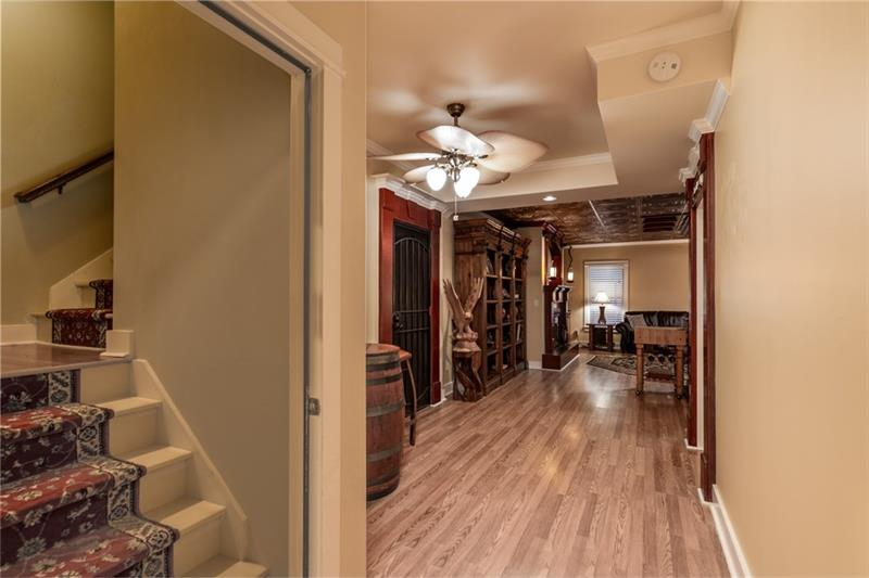 View of staircase leading into the terrace level.  Wine cellar to the left and media room located on the right.