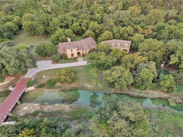 Gorgeous home on over 7 acres in the hill country w/creek. Interior includes massive, elaborate stone wall, open floor plan, soaring/vaulted ceilings & designer touches throughout. The spacious living rm features stone fireplace and opens to the gourmet kitchen w/luxury appliances & fixtures. Enjoy the screened-in porch w/fireplace & partial outdoor kitchen. The home office/4th bedrm features built-in bookshelves & spiral staircase up to the library. The apartment has 1 bedrm, bathrm, kitchen & living rm