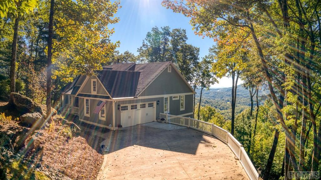Extremely light & bright big view home in immaculate condition located in the heart of Sapphire Valley. 3,700 ft elevation w/120 degree views all the way down into SC - you can see Lake Jocassee, Lake Keowee & the lights from Clemson! Great rm w/soaring cathedral wood ceiling w/accent beams & huge picture windows. Covered porch w/fan, skylights & covered decks. Storage galore & built-ins in great rm, kitchen & master bedrm. Master ensuite & additional guest room w/full bath on main level. Beautiful kitchen w/breakfast area overlooking the big views. Lower level features family room, another gas fireplace, mini-kitchen, another guest bedrm & 2nd master bedrm w/full bath. Family rm opens to spacious covered deck. Very fresh, clean & move-in condition. Most furnishings available outside of real estate sale. All Sapphire Valley/Wyndham Resort amenities include:  2 outdoor + kiddie pool and one indoor pool, saunas, hot tubs, weight room, game room, video rentals, running track, kids playground, Horsepasture River picnic grounds, board games, ski slope, tubing and zip-line areas, tennis center and golf course with driving range, Fairfield Lake access to swim, canoe, paddleboat, picnic and much more. Sign up for trips to local waterfalls and other local outings. Perfect for year-round families or seasonal retreat. Mountain enjoyment at its best!