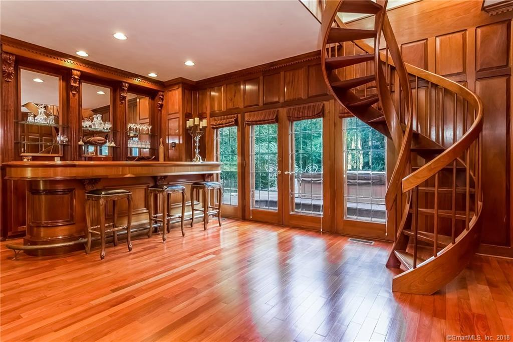 This exquisite custom Peter Smith Tudor style home is set on over 4 acres offering the utmost privacy within a short distance to the village center of Madison. The remodeled eat-in kitchen has cherry inlaid cabinetry, curved breakfast island, granite counters with solid granite backsplash, built-ins with wet bar and a fireplace. The showstopper of this home is the large mahogany paneled family room with mahogany bar and spiral staircase to the master suite and French doors to the hot tub which is located on the bluestone patio outside of the bar area.  This room also contains a floor to ceiling stone fireplace as does the large formal living room which is located off of the family room.  Off of the kitchen you'll find a covered porch with heated tile floors and sliders to either the hot tub area or the pool area. The master suite contains a bedroom with gas fireplace, remodeled marble bath with steam shower and heated tile floors, sitting room, custom cherry inlaid closet room with gas fireplace and tv with surround sound. The 3rd floor has two finished spaces that can be used as guest rooms.  The basement has a large game room with pool table as well as an exercise room. The exterior has professionally landscaped grounds, built-in heated pool, pool house with changing rooms, 6 zone irrigation and outdoor speakers. Sirius sound system and 6 hardwired Logitech cameras that can be accessed from your smartphone or computer.  The home also features a whole house generator.