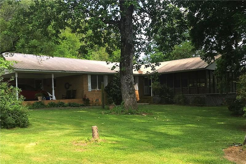 This charming ranch has the appeal of a rural setting and the convenience of being minutes away from interstate 75!  The home features 2 workshops, large level front yard and fenced back yard, 2 COVERED PORCHES, an office, open floor plan with a spacious living area, plenty of wooded acreage suitable for hunting...there are too many features to name here!! You have to SEE it and once you See it you will LOVE it!