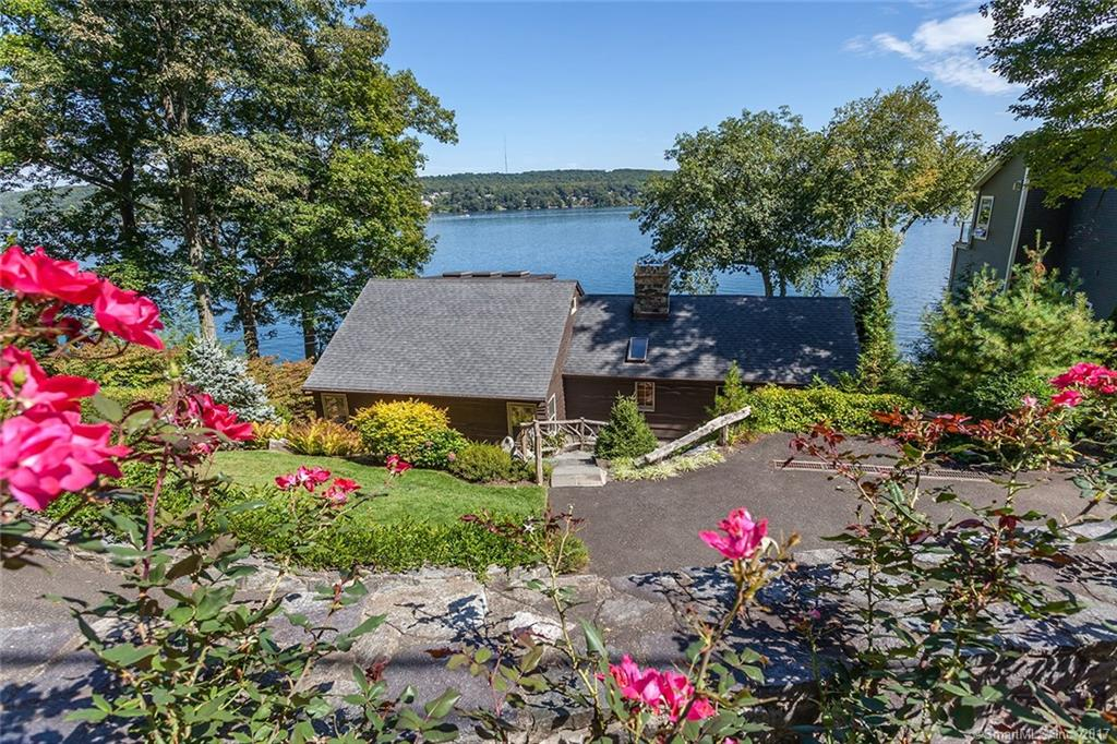 """Idyllic Candlewood Isle is home to this charming lakefront 3 BR, 2 Bath Contemporary cottage with paved drive, stone walls, custom walkways and handrail plus extensive updates. A charming great room, surrounded by walls of windows, creates that """" on the water"""" feel. The vaulted dining room offers beams, full stone fireplace and sliders to the deck w/expansive lake views.  A newer galley kitchen offers an efficient plan, granite counters, custom cabinets & stainless appliances. The spiral staircase leads to an enticing private master retreat w/updated spa bath. Back on the main level,l two additional, well appointed bedrooms wth hardwood floors and stunning new bath offer room for family or guests. Optional outdoor relaxation or dining al fresco, can be found in the spacious screened porch.  Community amenities of tennis, beach, clubhouse, basketball & summer camp for children make this your best choice for lakefront living at a great value!  Reduced over $130,000....  Come and see this great waterfront value!"""