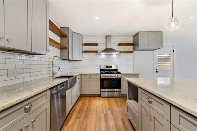 Amazing contemporary kitchen remodel features exposed shelving, downdraft, subway tile, high-end graniet, new cabinetry with hardware, farm style 100% sink, pendant and recessed lighting - all open to dining and living