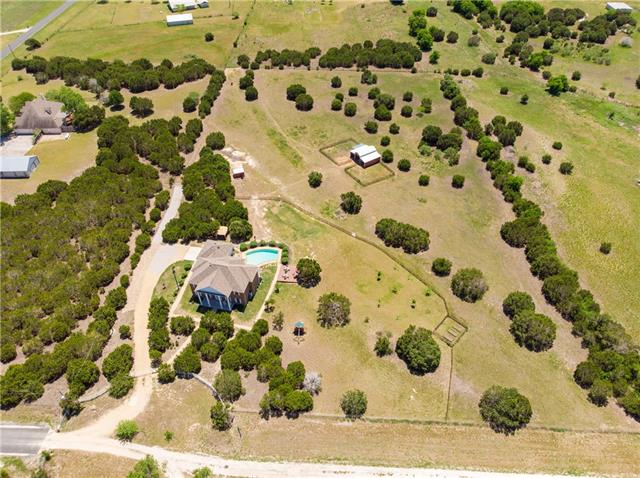 Don't want a cookie-cutter home in a cramped subdivision? Then check out this beautiful stately home on 5.5 acres w/ fabulous pool. This custom home boasts 4 overly-sized bedrooms & 3.5 bathrooms. The open kitchen is equipped with stainless steel appliances, quartz counter tops & soft-close cabinets. The master bedroom features 2 walk-in closets, soaking tub, walk in shower & dual vanities. Cool down in the swimming pool while enjoying the patio & sun deck. Located minutes from town & in Liberty Hill ISD!