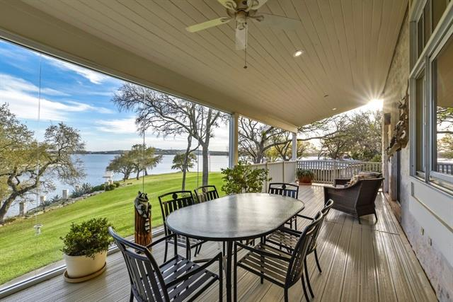 Spanning almost 5 acres on a Lake Travis peninsula that stretches along 830' of waterfront, from a peaceful inlet towards main body front, this Texas Country lake house is primed with some of the best Hill Country lakeside scenes. This serene home blends beautifully with the property that overlooks the wide-stretching lawns. Includes detached 1BD/1BA guest house and boat dock with 2 boat slips, jet ski ramps, storage and deck. Optional additional purchase of adj' tract MLS#2173173