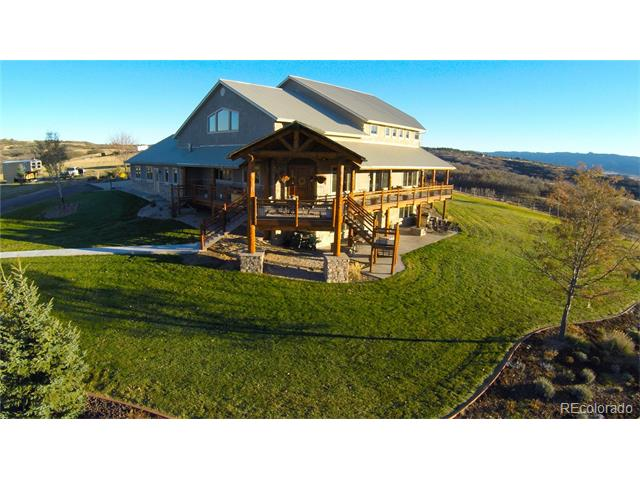"""40 magnificent rolling acres located in the highly desirable Plum Creek Valley on Hwy 105 (aka Perry Park Road). """"The Lodge"""" a vast expansive open floor plan with exposed log beans and pine tongue n' groove ceiling. The warm and inviting atmosphere is captivating and will make all your guests feel right at home. Gourmet Colorado kitchen featuring Alder cabinetry and a custom handmade center island with 2"""" beautiful slab granite counter-tops, farm sink, stainless steel appliances including a Fisher & Paykel double oven and 6 burner cook-top. Main floor master retreat offering a private entrance to the wrap around covered deck. Sitting area, gas fireplace, media access and open to the enormous master bath. *Walk-out level boast a 2nd full kitchen - dining space or board game central - Billiard area (or work-out space) - Media area ....great for your favorite movie or ball game....plenty of space to turn it UP. 4 fireplaces: 2 interior and 2 exterior. Laundry on main and walk-out level"""