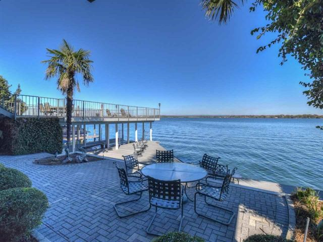 This home has spectacular north facing open water views. Main level includes open family room, wet bar, kitchen, dining & large master suite. Upstairs has 2nd family room & 3 bedrooms/ 3 baths, one of which is 35'x22' currently being used as combo bunk/game room & media room w/wet bar and lots of storage. Enjoy outdoor living with two covered lake front porches extending the width of the house on each level, both having access to a large open deck over the boathouse.