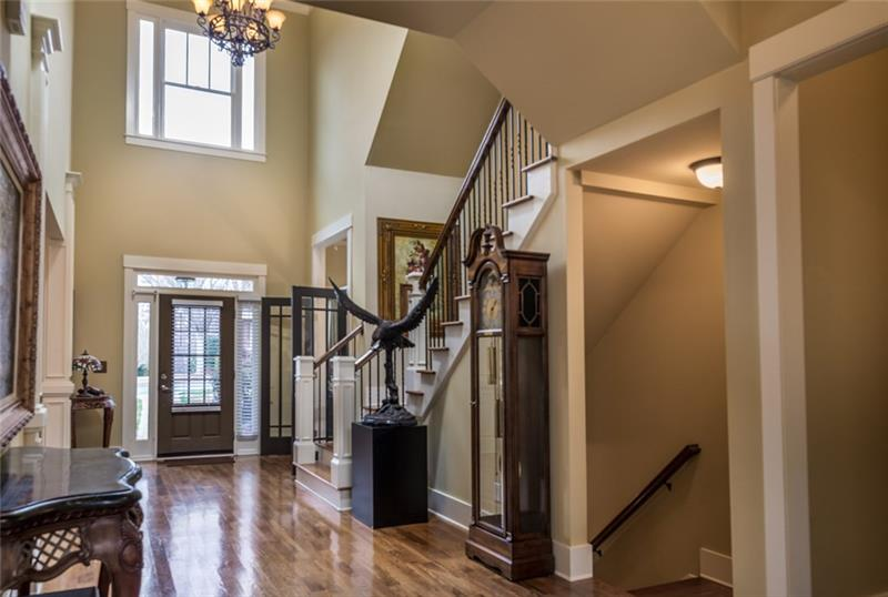 Open two story foyer with hardwoods through out with hardwood staircase with wrought iron spindles. Owner's suite on the main to the right of this picture.