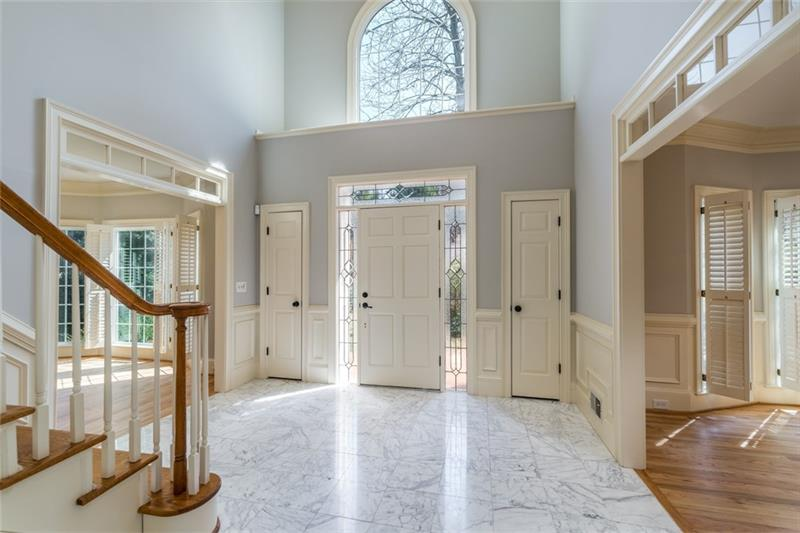 Gorgeous marble foyer with neutral palate with formal living off to right; accented by marble fireplace!