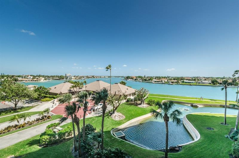 PRICE REDUCTION!! Panoramic water views from this St. Pete Beach Yacht & Tennis Club home will make you feel like you've graduated into the Ivy League of condo living.  Located just steps away from the sandy, Gulf beaches of Treasure island, this gated community features 7 Har-Tru tennis courts with boat slips that may become available for purchase. Situated on the 4th floor of The Constellation building with sweeping views of the intracoastal, this furnished condo offers a north-facing covered patio with a calming sea breeze. The master bedroom views span over water  and possesses an en-suite bathroom with a spacious walk-in closet. A generously sized second bedroom offers ample closet space and large windows. Spend your mornings watching the boats churn the waters below and your evenings watching the setting sun cast its colorful rays on the tides. The active community center boasts of a full gym/workout facility, a heated pool and spa overlooking the intracoastal waters and private men/women's saunas. Currently under renovation, there is a reservable, waterfront room available for private parties and grills available for waterside cooking and dining. The St. Pete Beach Yacht & Tennis club is a gated community offering 24/7 security and an on-site management company. This is not just a condo, it's a lifestyle. Make your appointment today!