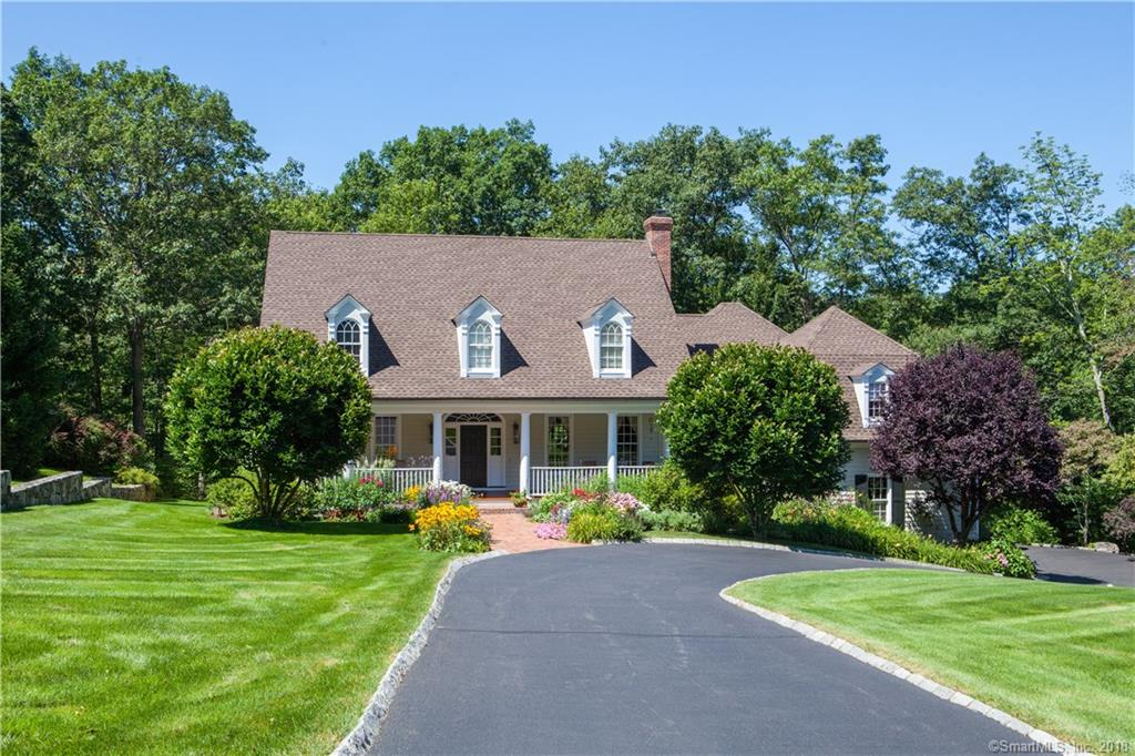 Mere minutes from Main Street sidewalks, this exceptional expanded cape sits on a quiet access way off of one of Ridgefield's most desirable streets. You are welcomed onto the full width front porch, newly refinished with wide board mahogany floor. This is the perfect place to relax and renew overlooking the expansive front property with spectacular perennial gardens and formal brick walkway. Enter into the two story foyer with beautiful compass rose floor. Light, bright and open, the main level features high ceilings, custom millwork, abundant builtins in most rooms. Natural light from a wall of windows and French doors floods into the comfortable 2-story family room space. An open floorpan allows for ease of living and entertaining. Interior features include: 2 fireplaces, French doors from FR and main level MBR to lovely deck for outdoor living, oversized bonus room/family room accessible from main and upper levels and a finished LL with optional 5th bedroom with full bath and French doors to a stone lower level patio. Improvements include: new roof, newly updated kitchen and fixtures, master bath updates, new guest bath and much more. Quality details in each room, this home offers gracious living spaces for all ages and stages 60 minutes from Mid-town Manhattan! The amazing curb appeal will call you home, come for a visit and stay for a lifetime.