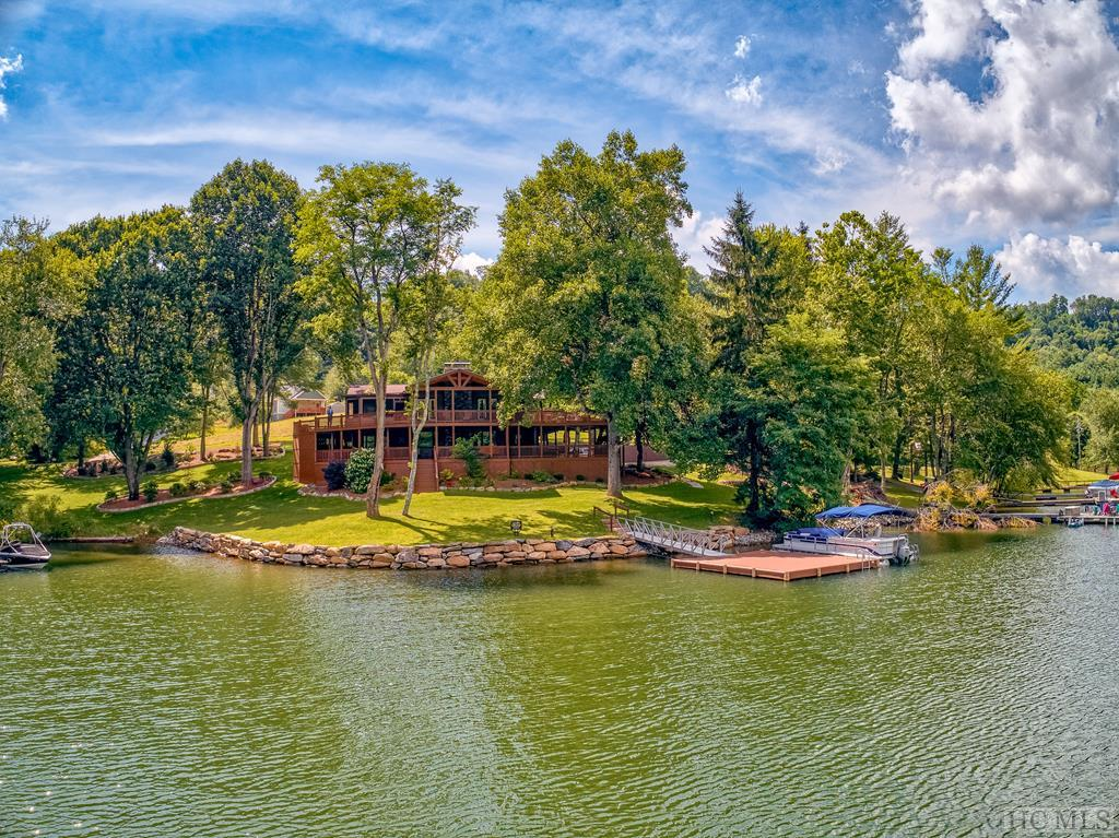 Expansive premier lakefront home on Lake Glenville.  300 feet of seawall lake frontage with panoramic lake/mountain views, multi-car parking areas, and attractive landscaping.  Possibly the easiest walk from home to dock on the lake.  Large two level deck can accommodate a large number of family and guests, there's a fire pit for gatherings on cool lake evenings, and the private dock is the largest permissible on Lake Glenville.  The dock has splinter free, color fast Trex decking, and an aluminum walkway for minimal maintenance.  The main level greatroom is an open floor plan with cathedral ceiling, stone fireplace, and oversized windows to bring the beautiful views inside.  The main dining, just off the kitchen, is adjacent to additional screened-in outside dining.  The completely updated chef's kitchen includes new granite countertops, new cabinets, LED lighting, and all professional Viking appliances, including a six-burner range.  The master and guest bedrooms, two flex rooms, and laundry space are on the main level, which has two full updated tile and granite baths. Top down shades allow natural light while preserving privacy.  Downstairs is a full living suite, with kitchen and appliances, game room with three-way table, guest bedroom and full bath, and family room with window seats and theater sound, all opening to a covered deck with swing, seating, and access to the dock.  Topping all this off is a two car garage with workbench, lockable tool storage, and an overhead secured storage space.  Additionally, there are two lighted exterior storage sheds with power outlets.  Sold completely furnished, with rooftop Direct TV receiver and dedicated entertainment system.  Broadband internet service is through a local proprietary provider.  One mile to Arrowhead Stables, 1.5 miles to Duke Power's sand beach and protected swimming.  Exceptional rental history available on request.
