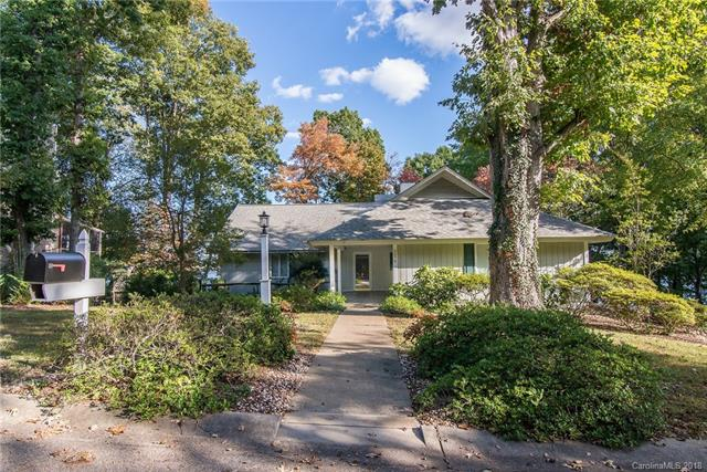"""If spectacular lake views are important to you, this may be the peninsula home you've been waiting for!  Watch the sun rising, and the beautiful colors of the sun setting daily on the main channel of Lake Wylie!  This lake house has it all- VERY unique architectural detail, beautiful hardwood flooring, soaring brick fireplace, exposed beam cathedral ceilings, floor length windows, open & level floor plan, mature landscaping w/gardenias & azaleas, and handicap access.  The lower level bedroom en suite provides privacy for guests or family members, and could be a home office, provide in-law living, """"man-cave"""", etc!  Lower level is connected w/fully roofed exterior stairwell.  Expansive lake viewing on a quiet corner lane w/a park view in front of the home.  There is a main level 2 car semi-enclosed port, a driveway and guest parking pad. Huge basement workshop, a screened porch and upper deck, w/ a covered patio on the walk-out lower level.  Tons of storage/very large closets."""