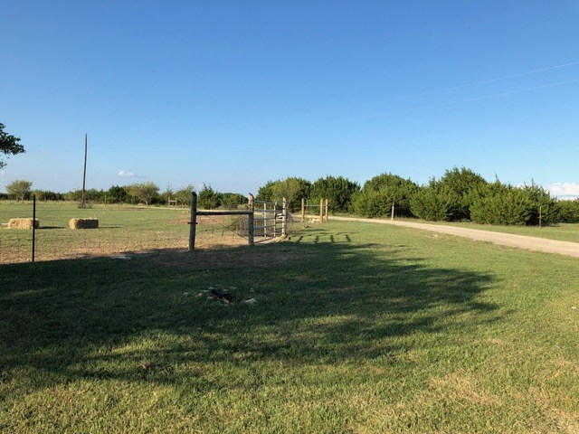 Lovely 10 acres just minutes from Hwy 183 extension. Includes 2,700 sq. foot slab. Water, sewer and propane ALREADY installed.  Also, renovated, 2nd story apartment w/ stainless appliances, granite, new flooring & built-in shelving & beds. Acreage is fenced and gated. Animals negotiable. 2nd year of Ag Exception. Surrounding homes are well-maintained. The sunsets can't be described.