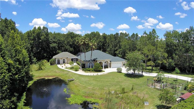 PRIVATE GATED HOME with POOL/SPA on over 3 ACRES, SEPARATE GUEST HOUSE with a BONUS ROOM, NEW ROOF, NO DEED RESTRICTIONS, and a picturesque CONSERVATION VIEW. Your living the good life in this marvelous and rare 3048 sq. ft. 5-bedroom 3-bath pool home plus a separate 1319 sq. ft. 1-bedroom 1-bath guest house which includes a bonus room. This beautiful home offers formal living & dining rooms along with a separate family room. Oak hardwood flooring & volume ceilings flow throughout home. All bedrooms have new carpet. The family room includes built-in accent/TV wall, plant shelves and art niches along with a beautiful view of the pool. You can't miss the gorgeous kitchen filled with raised panel cabinets accented with Corian countertops, island prep cabinet, built in desk, breakfast bar and nook seating.  The newer stainless-steel Bosch induction cook-top range, double oven, & dishwasher will stay! French doors lead into the sizable master bedroom and the master bathroom includes a walk-in shower, Jacuzzi tub, his and her separate vanities and walk-in closets.  The remaining 4 bedrooms are each roomy, with plenty of closet space too. Relax and unwind by the salt water pool and enjoy the quiet and peaceful conservation view. The GUEST HOUSE is handicap accessible and includes new carpet, spacious living area, kitchenette, a 18x15 bedroom, walk-in closet, bath with beach entry walk-in shower, and separate bonus room/game room. No HOA, deed restriction or CDD fees! To many highlights to mention. Come see it!