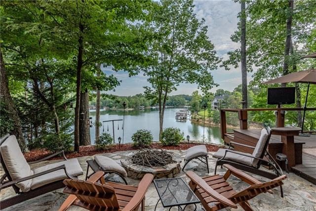 WATERFRONT on Lake Wylie in Tega Cay, SC.  Views of Windjammer Cove from almost every room!  Stunning hardwood floors throughout this custom remodel & addition in 2008. Amazing Outdoor Living! Stone patio with built in stone seating & fire pit, covered stone outdoor game area, deck, patio with 2nd fire pit, covered deck off the great room with ceiling fans & lake views, tiki bar by the dock. Surround sound through out & by the lake! Sound system in the office closet will convey; system integrated with wall switches.  Gourmet kitchen, stainless appliances, granite, gas professional cooktop, island bar seats 5, wine fridge. Open floorpan to great room has double sided gas fireplace. Five Bedrooms, Bedroom 4 has it's own private bath. Master steam shower. Lower level bonus/ family room with tile floor & wet bar. Heated & cooled outdoor full bath for coming in off the lake. Covered dock, boat lift, wooded area, plenty of storage. Central vac, Rinnai tankless hot water. Fort Mill Schools.