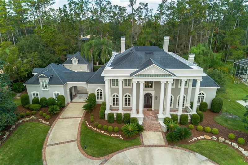 """Welcome to one of the most beautiful homes in the area, towering oaks and a gently rolling lawn are the perfect backdrop for this classic Georgian style residence. Designed by an Atlanta architectural firm, this beautiful and timeless estate home is graced with a custom floating staircase and two-story exterior columns. The two-story foyer presents a stunning introduction to the open floor plan and the natural light-filled two-story """"grande room"""" just beyond. Wood flooring expands throughout the first floor. The upstairs offers four large bedrooms. Architectural details are an integral part of this majestic home and are evident throughout. Pella architectural windows add to the feeling of richness and quality. A spacious, open kitchen showcases upscale appliances and the abundant, elegant wood cabinetry accentuated by rich colors of designer granite. The light and bright family room overlooks the pool and open brick porch. The two separate garages, accessed by a porte-cochere, offer second story carriage-house living with a bedroom or bonus area and full bath. Located on a wooded acre in a gated, golf community, this elegant home is truly spectacular and exudes charm, warmth and quality."""