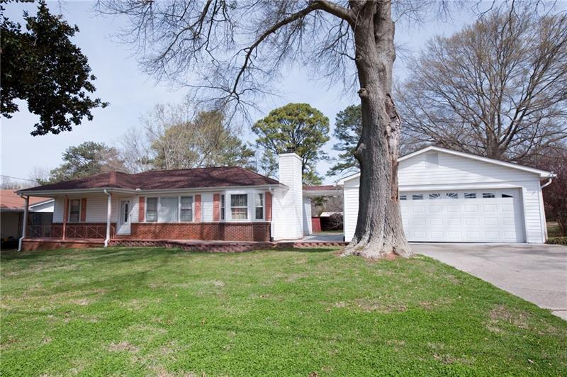 Attn INVESTORS: Tenant occupied home paying $1332/mo. PLUS this ranch home w/ front porch on DOUBLE LOT, outbuilding (barn)+ storage, big yard and sits across the street from Mableton Amphitheater! Hardwoods over most of the house. Den w/ fireplace, laundry room, separate dining room, living room. HUGE deck overlooking yard. Detached 2 car garage. Close to shopping, restaurants, post office and I-20. Enough land to build another home, workshop, garage, or whatever makes you happy!  Call for details. Layout sketch in photos.