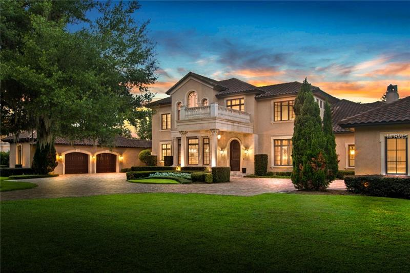 An elevated living experience awaits in one of Florida's most prominent locations. Featuring over 10,000 sq. ft. of exquisitely appointed living space, set on over 2 privately-gated acres with panoramic views of famed Lake Butler, this spectacular residence will captivate at every turn. Enchanting views & spacious indoor-outdoor spaces, united by walls of sliding glass doors, create a seamless connection to the nearly 365 ft of private water frontage with dock. The terraced patios, sunken summer kitchen, swim-up pool bar, natural rock waterfall, & meandering pool evoke a private resort, blending perfectly into the natural surroundings. Inside, open entertaining spaces feature the highest standards of materials, such as custom millwork, Italian flooring, one-of-a-kind fixtures, & European appliances. A voluminous first-floor owner's retreat beckons with large entry hall, 2 fireplaces, and a private living room with custom morning bar...all opening to multiple private terraces and pool beyond. The second story, completely reconfigured & expanded by the current owners, offers 3 spacious ensuite bedrooms plus media room. The estate is also graced with distinctive details such as 5 fireplaces, an elevator, wine room, multiple wet bars & private office. A renovated separate guest house sits to the rear of the property with lake views. Enjoy the serenity of the established community & 24-hour guard-gated security, just minutes from Orlando's world-class attractions, golf courses & international airport.