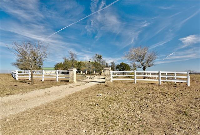 """This is an outstanding commuter ranch very close to Austin with an unbelievable feel to it with long range vistas from the custom ranch house and the pasture is pristine. All minerals convey as family is liquidating the family estate. The house is in """"As is"""" condition. 2 ponds on it, 35 minutes to downtown Austin, 5 miles from Toll 130. Detached workshop and gun shop. Thereisover$5500amonthincomewithestablishedtenantsinplaceahugeplus. A must see!Huge vaulted Great Room and huge open fireplace and kitchen."""