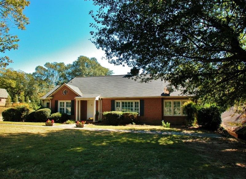 """So much potential w/this classic Gainesville home! Paver walkway leads to the front door. Hardwood floors, large windows & so much space! 2/1 on the main w/ a formal dining room, kitchen, office, study, & laundry. 2nd floor is the master wing"""", featuring a large jetted tub & spacious bedroom. Terrace level is a home in itself offering a 2nd kitchen, family room w/fireplace, and 2 bedrooms plus storage! Step out back to find the beautiful back yard and pool! All of this on an oversized lot, right in the middle of downtown Gainesville, on one of the most desired streets!"""