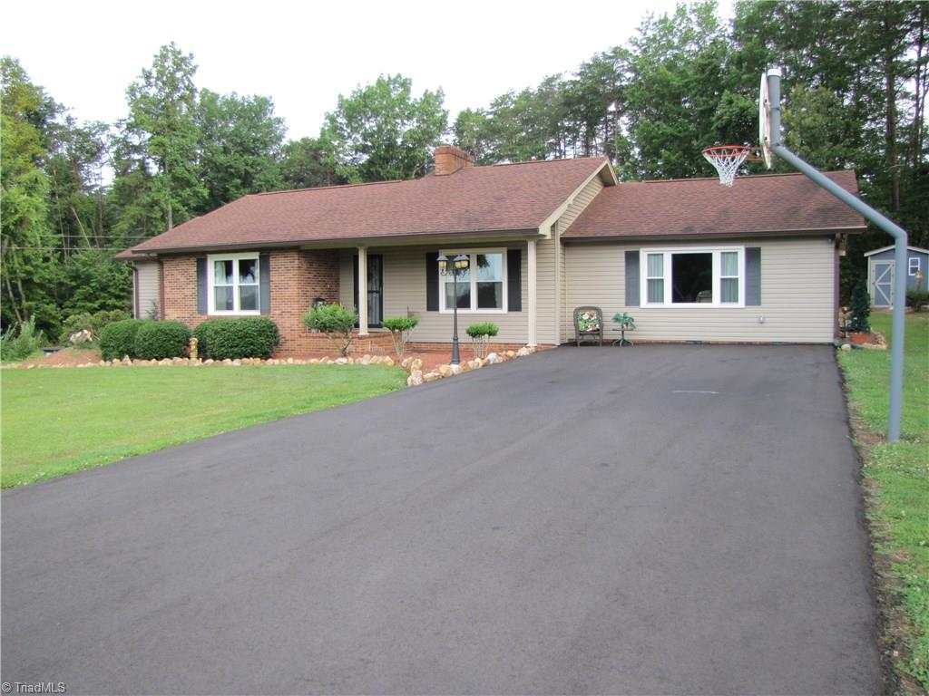 H-3299 WOW two homes! Country home with view of Pilot Mountain. Ranch home features 3BR/2BA, fireplace in LR & den. Large master suite 20' X 20'. Basement den with bar great space for entertaining. Basement garage/workshop. 10 year old mobile  with 3BR/2BA, new refrigerator, walk in tub, and screened porch could be used  for parents or returning children.  Storage building with lean too. Mature landscaped yard. Sellers will give $5000 allowance.