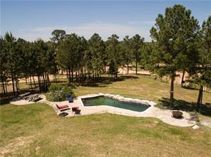 MUST See! 90+ acres of Lost Pines paradise with ROLLING HILLS just outside Forbes Magazine #1 fastest growing city in America - Austin, TX (30 miles from Austin airport, 24 miles from The Circuit of Americas, 90 Minutes to The Riverwalk in San Antonio, and 2.5 hours to Houston).  Two large ponds (one spring fed) and three smaller ponds, a wet weather creek lined with pine trees, and abundant wildlife you will find on this manicured fenced property.  In-ground pool*10 RV hook ups*Work shop*Much more!