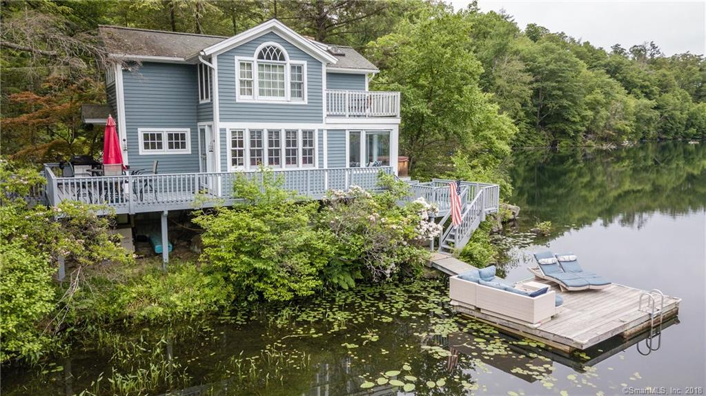 This adorable lake cottage sits directly on pristine, spring-fed Green Pond with views from every room. You will fall in love with this private, 1-acre property that boasts 390 feet of water frontage with two docks in the gated community of Candlewood Lake Estates. Relax in your hammock while listening to the soothing sound of your own babbling brook and waterfall. Sip your morning coffee on your deck and watch the day unfold on this gem of a lake, the cleanest in Connecticut.  Quiet and removed from the noise of the boats on Candlewood, yet within walking distance of the community docks and beach. There are four beaches in Candlewood Lake Estates - 2 on Green Pond and 2 on Candlewood. Canoe, row boat and paddle boat included! Outdoor shower, Generac full house generator, hot tub, complete water-filtration system and garage renovation are just some of the updates in this wonderful weekend getaway. Garage has lift- can fit a SUV plus smaller vehicle on lift!.Activities: Appalachian Trails; Farmers Markets; Antiquing; Connecticut Wine Trail; Star Gazing; Connecticuts Largest Flea Market (The Elephants Trunk Bazaar); Sherman Playhouse Live Theater; 28 mi. Scenic Drive North on Route 7 ( see covered bridges and Bald Eagles along the way).Movie theater, restaurants and shops in nearby New Milford.