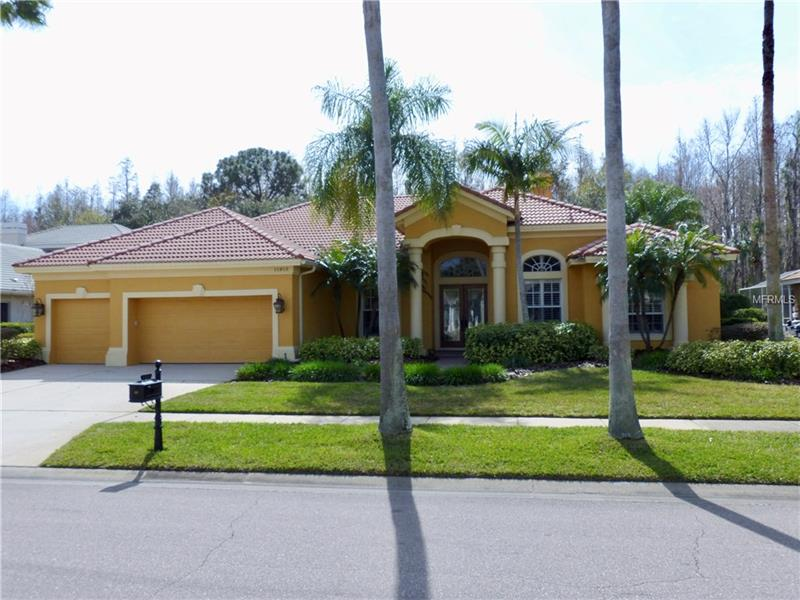 """Drive through the privacy gates to find this custom Mediterranean style executive home in the desirable Estates section of Harbor Links in Westchase.  Look up as you approach the outside foyer at the cypress wood ceiling.  Enter through the 8"""" double doors into the open foyer, living room, and dining room areas, with their 12' to 14' ceilings.  Enjoy the cozy, gas/wood fireplace while taking in the spectacular pool and conservation views through the french doors.  A day at the office is easier in this study with coffered ceiling and hand scraped wood floors.  When work is done, retreat to the master suite with hardwood floors and custom closet.  Then move on to the travertine floored master bath to relax in the soaker tub. The kitchen will delight you with it's custom cabinets, granite counters, large island, and Wolf wall oven, microwave, warming drawer and gas cooktop.  Continuing the open feel is the family room with 12' pocket sliders.  Go outside to the expansive lanai, with it's heated PebbleTec salt water pool/spa, and outdoor kitchen/lanai finished overhead with more cypress wood. Back inside you'll find 3 more bedrooms with hardwood floors and custom closets. The bonus room, with vaulted ceiling, sliders to the lanai, and wood floors, can be set up as a 5th bedroom or whatever else your needs may be. The 3 car garage, with it's professionally done epoxy floor, storage racks and flexible shelving will fit all your toys.   Too much more to mention here, you really need to view this property."""