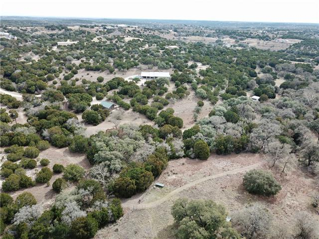 36.883 Acres in high-growth Dripping Springs! 1 mile off Hwy 290 & 1.5 mile to Belterra commercial. Use as private ranch, or develop. Limited restrictions in the ETJ! 60' of road frontage leads to the set-back acreage. Multiple build sites. Existing structures include 2700/sqft main home w/ converted garage as guest suite. (4 BRs, 3 Bath total.) Detached 700/sqft cottage w/ full kitchen, bath, living/dining, and bedroom. B&B income potential! Wildlife Exempt in place means LOWER TAXES.